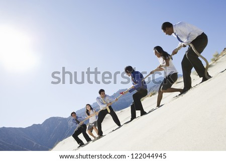 Low angle view of multi ethnic business people playing tug of war in desert - stock photo