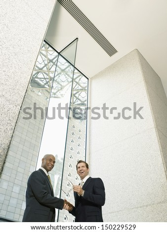 Low angle view of multiethnic businessmen shaking hands in office building - stock photo
