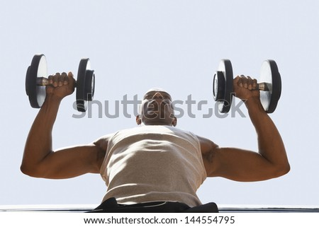 Low angle view of muscular man lifting dumbbells against sky - stock photo