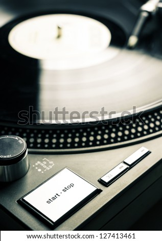 Low angle view of old fashioned turntable playing a track from black vinyl. Start-stop button in focus. - stock photo