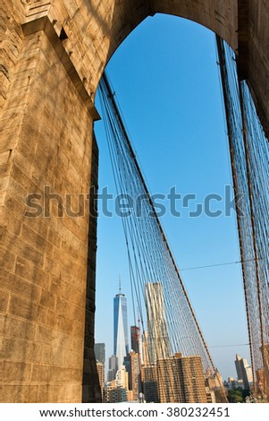 Low Angle View of One World Trade Center Skyscraper Amongst Manhattan Buildings as seen through Arch on Brooklyn Bridge, New York City, New York, USA - stock photo
