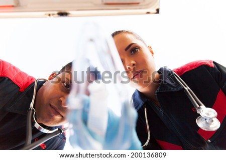 low angle view of paramedics putting oxygen mask on patient - stock photo