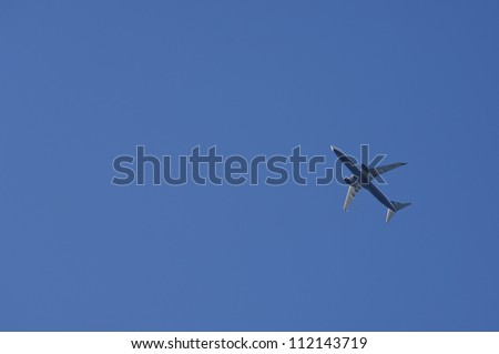 Low angle view of passenger jet flying against blue sky