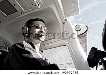 Low-angle view of pilot in cockpit of single-engine aircraft