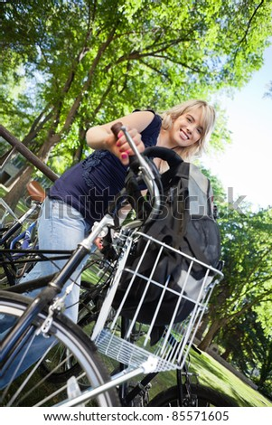 Low angle view of pretty female student standing with her bike - stock photo