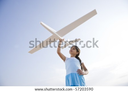 Low angle view of pretty 9 year old Hispanic girl playing with toy model airplane - stock photo