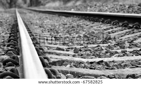 Low Angle View of Railway Tracks in Black and White with Shallow Depth of Field - stock photo