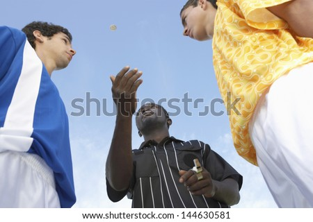 Low angle view of referee flipping a coin before the football game - stock photo