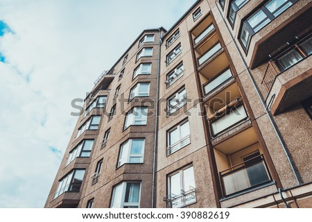 Low angle view of residential apartment building with bay windows and recessed small patios - stock photo