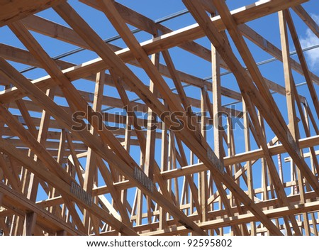 low angle view of roof trusses and framing of new house construction - stock photo