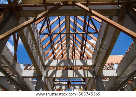 Low angle view of roof trusses and framing wooden of new house construction.