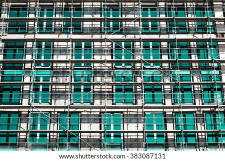 Low angle view of rows and columns of metal scaffolding over rectangular windows on building outdoors. - stock photo