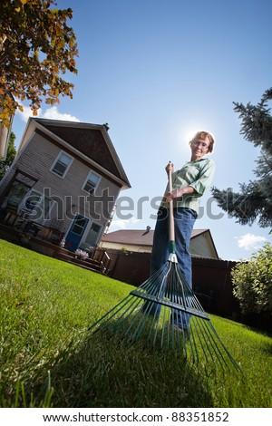 Low angle view of senior woman holding rake - stock photo