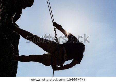 Low angle view of silhouetted man climbing rock against sky - stock photo
