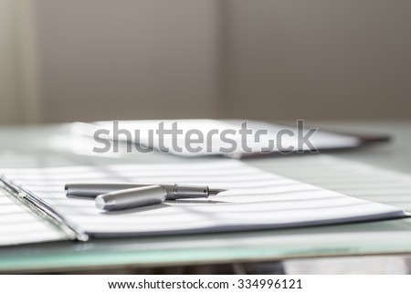 Low angle view of silver ink pen lying on white sheet of paper in a folder with another set of paperwork at the opposite side of the desk. - stock photo