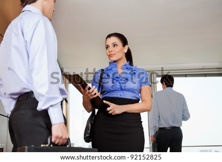 Low angle view of smart business woman standing with her colleague in office - stock photo