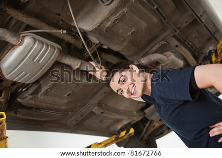 Low angle view of smiling young female mechanic repairing car in auto repair shop - stock photo