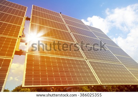 Low angle view of solar photovoltaic cell panels in bright sunlight.  - stock photo