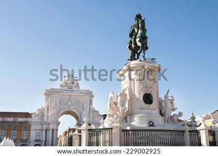 Low angle view of Statue of King Jose I and Rua Augusta Arch against clear blue sky; Lisbon; Portugal; Europe - stock photo