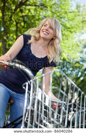 Low angle view of sweet female student riding a bike - stock photo