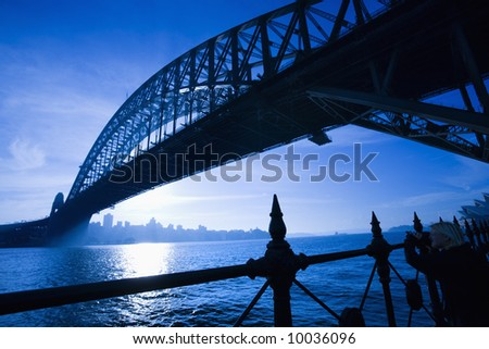 Low angle view of Sydney Harbour Bridge at dusk with harbour and distant Sydney skyline, Australia. - stock photo