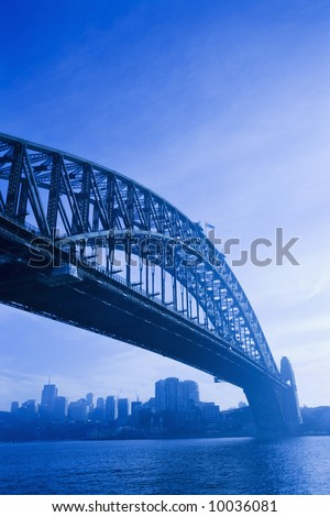 Low angle view of Sydney Harbour Bridge in Australia with view of harbour and downtown skyline. - stock photo