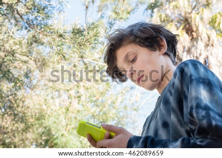 Low angle view of teenage boy in black tie dyed windcheater using smart phone with trees in background