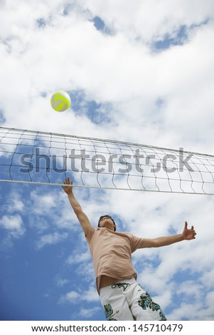 Low angle view of teenage boy playing beach volleyball against cloudy sky