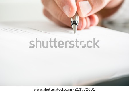 Low angle view of the fingers of a man writing on a document with a fountain pen conceptual of communication, correspondence, business agreement, legal contract or creativity. - stock photo