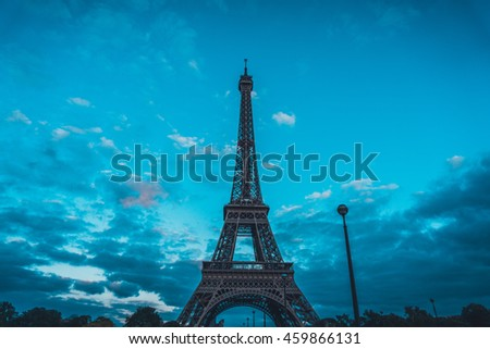 Low angle view of the iconic Eiffel Tower, Paris against a cloudy blue sky at twilight in a tourism and travel concept
