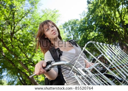 Low angle view of thoughtful female student standing with her bike - stock photo