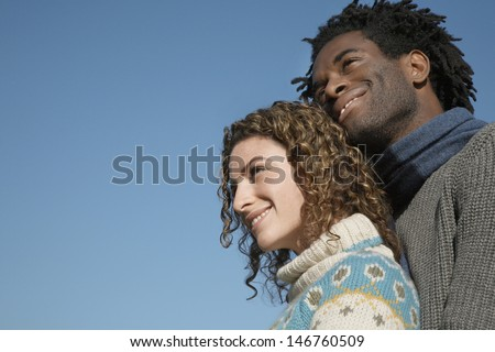 Low angle view of thoughtful young couple looking away against clear blue sky - stock photo
