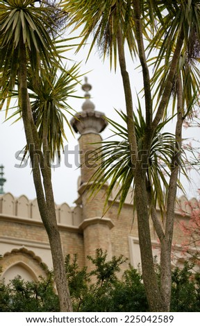 Low Angle View of Tropical Foliage and Architecture in Brighton Pavilion Gardens - stock photo