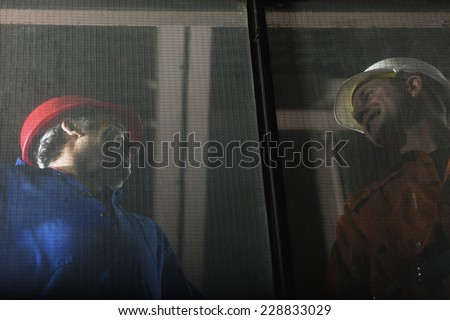 Low angle view of two factory workers seen through a screen panel - stock photo