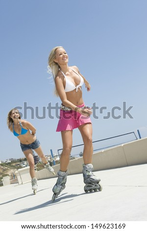 Low angle view of two happy young women on in-line skates - stock photo
