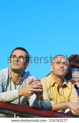 Low angle view of two men leaning on the railing of a patio enjoying a drink