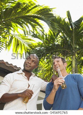 Low angle view of two multiethnic men with beer bottles against palm trees - stock photo