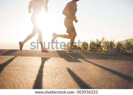Low angle view of two people running on country road at sunrise. Cropped shot of young man and woman jogging in morning, with bright sunlight. - stock photo