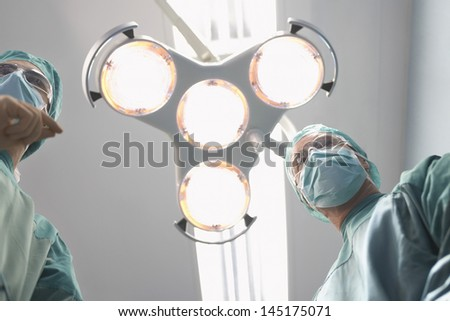 Low angle view of two surgeons under surgery lights in operating theatre - stock photo