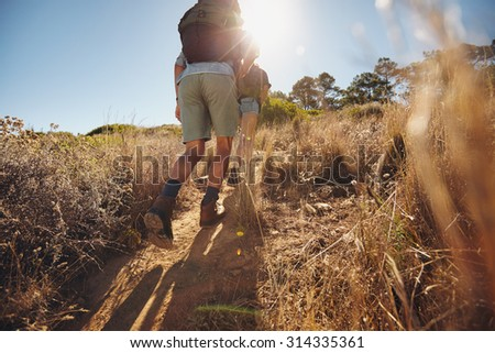Low angle view of two young people climbing uphill on a mountain. Couple on a hiking trip on a sunny day.