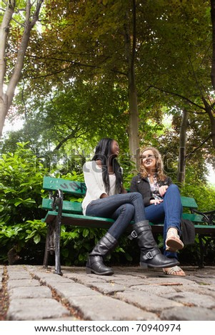 Low angle view of two young relaxed female friends chatting in the park - stock photo