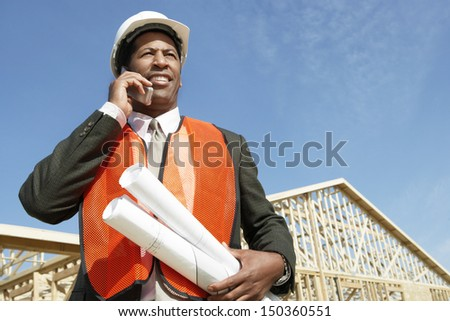 Low angle view of worker with blueprints using cell phone at construction site - stock photo