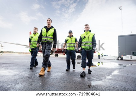 Low Angle View Of Workers Walking On Runway