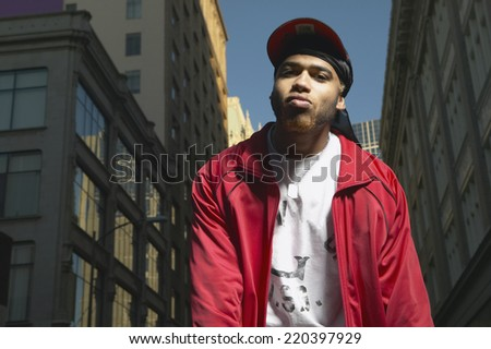 Low angle view of young African man standing in urban area - stock photo