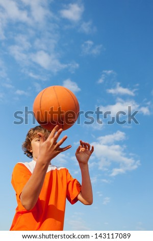 Low angle view of young basketball player spinning ball against sky - stock photo