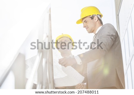 Low angle view of young businessman in hard hats reviewing blueprint on stairway - stock photo