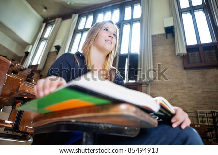 Low angle view of young college girl paying attention in lecture - stock photo