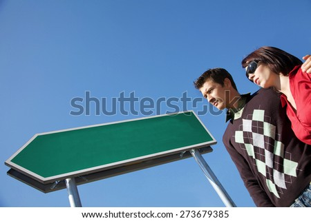 Low angle view of young couple with arm around - stock photo