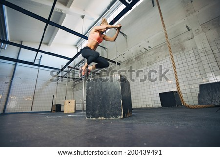 Low angle view of young female athlete box jumping at a crossfit gym. Fit woman is performing box jumps at gym. - stock photo