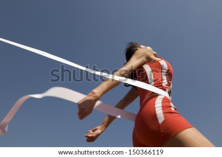 Low angle view of young female athlete crossing finish line against clear blue sky - stock photo